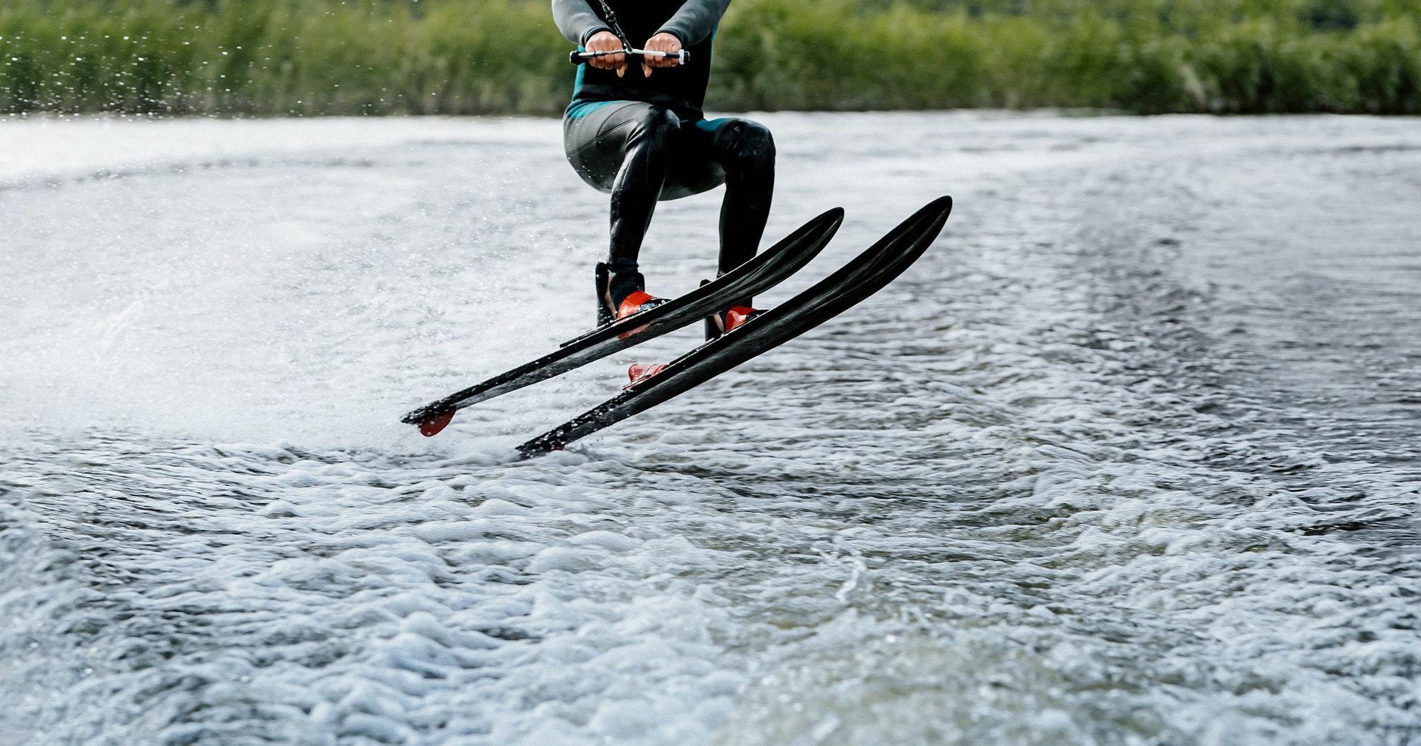 man waterskiing on lake behind boat
